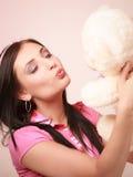 Muchacha infantil infantil de la mujer joven en juguete rosado del oso de peluche que se besa Imagenes de archivo