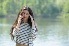 Muchacha infeliz con el teléfono móvil Fotos de archivo