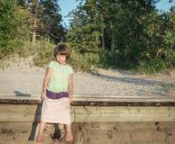 Muchacha infeliz del niño que se sienta en cubierta de madera cerca del bosque en el tiempo de la puesta del sol Imagen de archivo