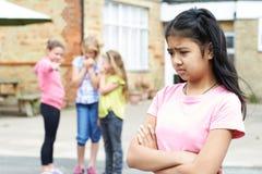 Muchacha infeliz que es cotilleada alrededor por los amigos de la escuela Fotos de archivo