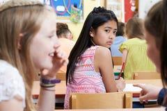 Muchacha infeliz que es cotilleada alrededor por los amigos de la escuela en sala de clase Fotografía de archivo libre de regalías