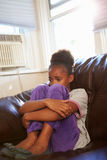 Muchacha infeliz que se sienta en Sofa At Home Imágenes de archivo libres de regalías