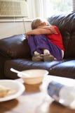 Muchacha infeliz que se sienta en Sofa At Home Imagen de archivo
