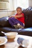 Muchacha infeliz que se sienta en Sofa At Home Foto de archivo