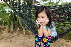 Muchacha infeliz que se sienta solamente en hamaca Al aire libre el día de verano imagenes de archivo