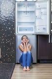 Muchacha infeliz y hambrienta cerca del refrigerador vacío Fotos de archivo libres de regalías