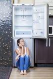 Muchacha infeliz y hambrienta cerca del refrigerador vacío Fotos de archivo