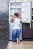 Muchacha infeliz y hambrienta cerca del refrigerador vacío Imagenes de archivo