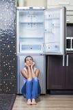 Muchacha infeliz y hambrienta cerca del refrigerador vacío Foto de archivo libre de regalías