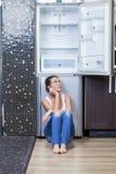 Muchacha infeliz y hambrienta cerca del refrigerador vacío Imágenes de archivo libres de regalías