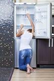 Muchacha infeliz y hambrienta cerca del refrigerador vacío Fotografía de archivo libre de regalías