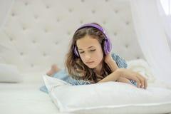 Muchacha inocente blanda que escucha la música con los auriculares que mienten en la cama blanca Imagenes de archivo