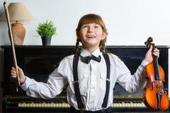 Muchacha inspirada y feliz que sostiene un violín interior Foto de archivo libre de regalías
