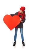 Muchacha integral que soporta un corazón rojo de la cartulina Imagen de archivo
