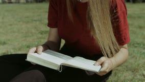 Muchacha inteligente que lee un libro al aire libre almacen de video