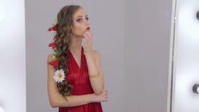 Muchacha inusual con maquillaje creativo en el vestido que mira su reflexión en espejo almacen de metraje de vídeo