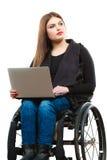 Muchacha inválida de la mujer en la silla de ruedas usando el ordenador Imagen de archivo