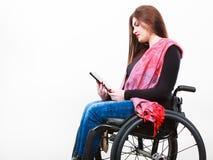 Muchacha inválida de la mujer en la silla de ruedas usando la tableta Imagen de archivo