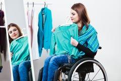 Muchacha inválida en la silla de ruedas que elige la ropa en guardarropa Fotografía de archivo libre de regalías