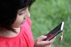 Muchacha Japonés-Rusa linda que juega con un cellphon Imágenes de archivo libres de regalías