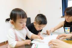 muchacha japonesa de 1 años y imágenes de 2 años del dibujo del muchacho con la madre Foto de archivo