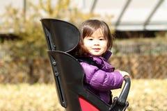 Muchacha japonesa en asiento del niño de la bicicleta Imagenes de archivo