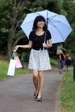 Muchacha japonesa hermosa que recorre con los bolsos de compras foto de archivo libre de regalías