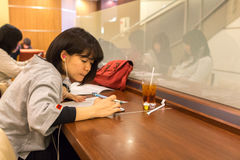Muchacha japonesa que se sienta dentro de una cafetería imagen de archivo libre de regalías
