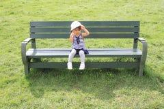 Muchacha japonesa que se sienta en el banco en el campo Fotos de archivo libres de regalías