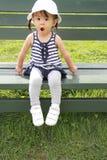 Muchacha japonesa que se sienta en el banco en el campo Foto de archivo
