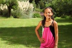 Muchacha joven alegre de la escuela que presenta en parque Foto de archivo libre de regalías