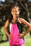 Muchacha joven alegre de la escuela que se coloca en el parque Imágenes de archivo libres de regalías