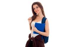 Muchacha joven alegre del estudiante con la mochila y los libros que sonríe en la cámara aislada en el fondo blanco años del estu Imagen de archivo