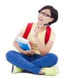Muchacha joven asiática del estudiante que se sienta en piso con el libro Imagen de archivo libre de regalías