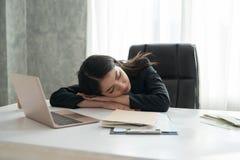 Muchacha joven asiática del negocio que duerme en el escritorio en frente un ordenador portátil Imagenes de archivo