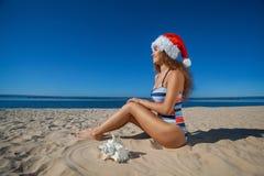Muchacha joven, atractiva en un bañador negro y sombrero de Santa Claus que se sienta en la playa, por el mar Imagenes de archivo