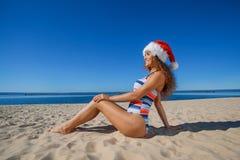 Muchacha joven, atractiva en un bañador negro y sombrero de Santa Claus que se sienta en la playa, por el mar Fotos de archivo
