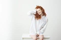 Muchacha joven blanda del pelirrojo en la camisa que se sienta en la tabla sobre el fondo blanco que ríe con los ojos cerrados qu Imagenes de archivo