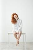Muchacha joven blanda del pelirrojo en la camisa que se sienta en la tabla sobre el fondo blanco que sonríe mirando la cámara Fotografía de archivo libre de regalías