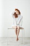 Muchacha joven blanda del pelirrojo en la camisa que se sienta en la tabla sobre el fondo blanco que sonríe mirando la cámara que Imagen de archivo