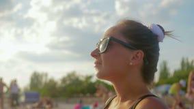 Muchacha joven, bonita en gafas de sol y traje de baño que disfrutan de la puesta del sol en la playa, ella mira el horizonte almacen de video