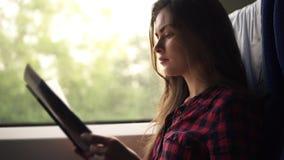 Muchacha joven, bonita que viaja en tren moderno El sentarse al lado de la ventana y lectura en camisa de tela escocesa Vista lat almacen de video