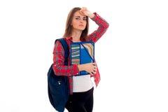 Muchacha joven cansada de los estudiantes con la mochila y carpetas para los cuadernos en sus manos que miran la cámara aislada e Fotos de archivo libres de regalías