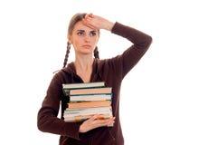Muchacha joven cansada de los estudiantes con muchos libros en sus manos aisladas en el fondo blanco Foto de archivo