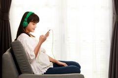 Muchacha joven de Asain que escucha la música con el auricular y el smarthpho Fotos de archivo libres de regalías