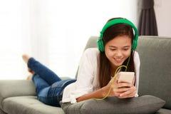 Muchacha joven de Asain que escucha la música con el auricular y el smarthpho Fotografía de archivo libre de regalías
