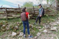 ¿Muchacha joven de dos turistas? viaje en el campo y coloqúese al lado de una cerca de madera vieja Imágenes de archivo libres de regalías