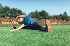 Muchacha joven de la aptitud que hace estirar en la puesta del sol Campo de fútbol Foto de archivo libre de regalías