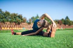 Muchacha joven de la aptitud que hace estirar en la puesta del sol Campo de fútbol Fotografía de archivo libre de regalías