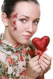 Muchacha joven de la belleza que lleva a cabo el corazón rojo Fotos de archivo